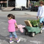 Young girl helps mom with the 'Flower Wagon' on 'Flower Day' at Eastern Market, Detroit, MI...